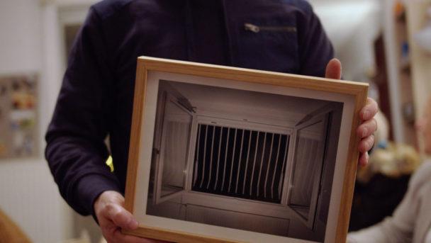 Karim Kal tenant une de ses photographies encadrées